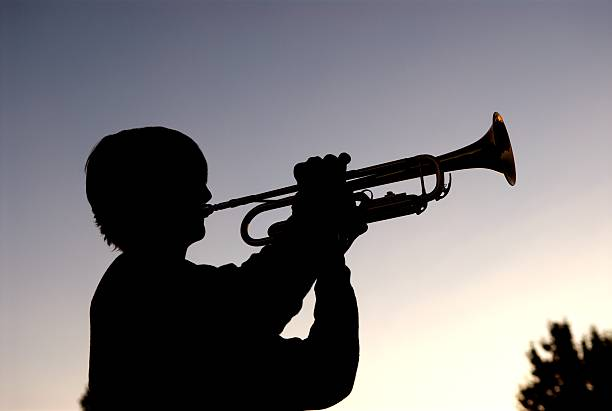 Dusk Trumpeter Silhouette of young trumpter at dusk. Amen stock pictures, royalty-free photos & images