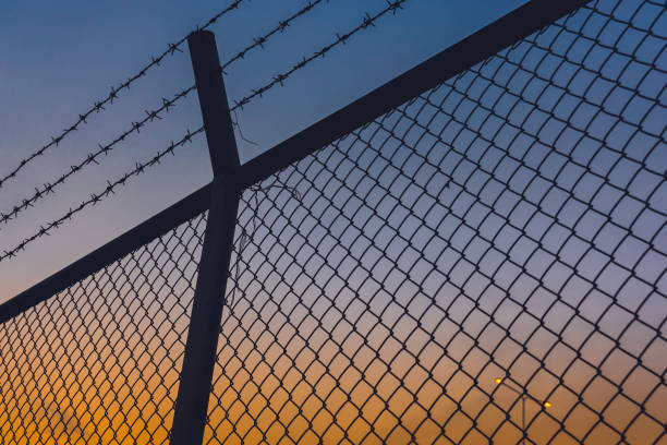 dusk twilight evening sky with fences and barbed wire wire dusk twilight evening sky with fences and barbed wire wire border patrol stock pictures, royalty-free photos & images