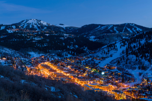 Dusk View of Park City Glowing.  Scenic village from above with cool blue dusk light and glowing warm lights.  Dusk View of Park City Glowing with lights.  Captured as a 14-bit Raw file. Edited in 16-bit ProPhoto RGB color space.