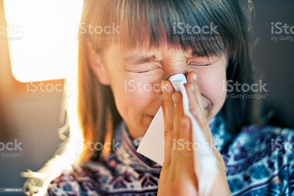 Dust allergy - little girl sneezing and cleaning runny nose stock photo
