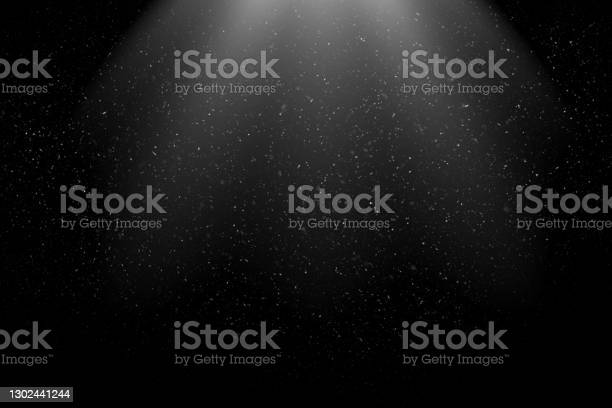 Photo of Dust Particles / Snowfall in the Light Beam against Black Background