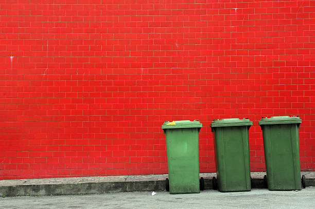 dustbin and red wall stock photo