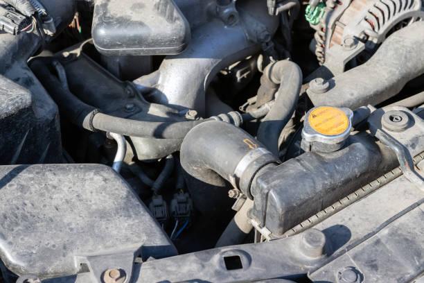 Détails poussiéreux d'un compartiment moteur de voiture plat-quatre (boxeur) sous le capot ouvert. Capuchon et tuyau de radiateur de voiture. Vue de plan rapproché sur une journée ensoleillée - Photo