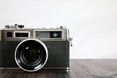 Studio shot of a dusty old vintage 35mm film camera on a brown table and white background front view close-up with copy space.