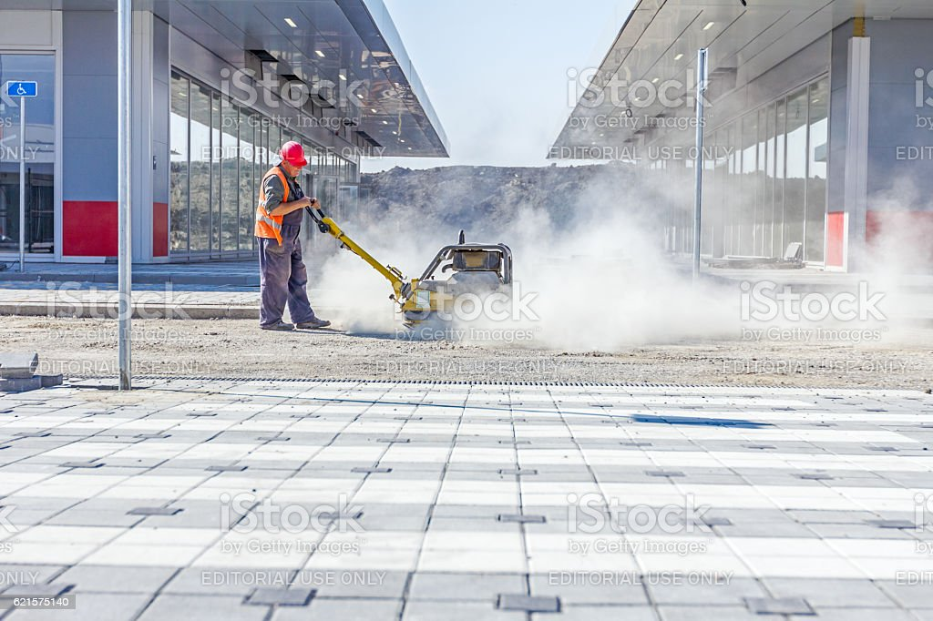 Dusty view on worker who controls vibration plate compactor stock photo
