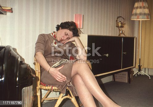 Dutch 1958 vintage image of a woman with magazine on lap sleeping in chair next to an old gas heater.