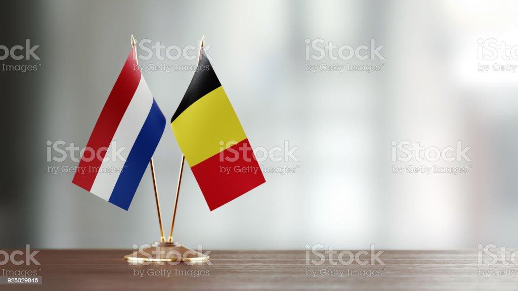 Par de bandera holandesa y belga en un escritorio sobre fondo Defocused - foto de stock