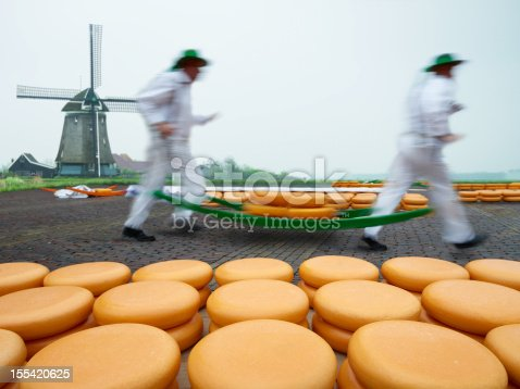 Dutch cheese market,, workers carrying a pile of cheese on a specially designed trolley hanging from their shoulders.