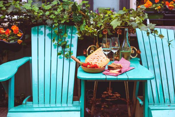 holländischer käse mit löchern und erdbeere. weißwein in ein glas und snacks. essen auf dem balkon, textfreiraum - französische land tisch stock-fotos und bilder