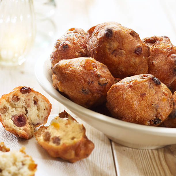 dutch doughnut with raisins - oliebollen stockfoto's en -beelden