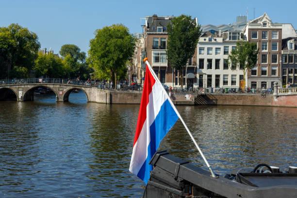 nederlandse vlag vliegen op boot op de amsterdamse gracht - keizersgracht stockfoto's en -beelden