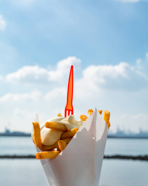 Dutch french fries from mashed potato with mayonaise and plastic fork on top stock photo