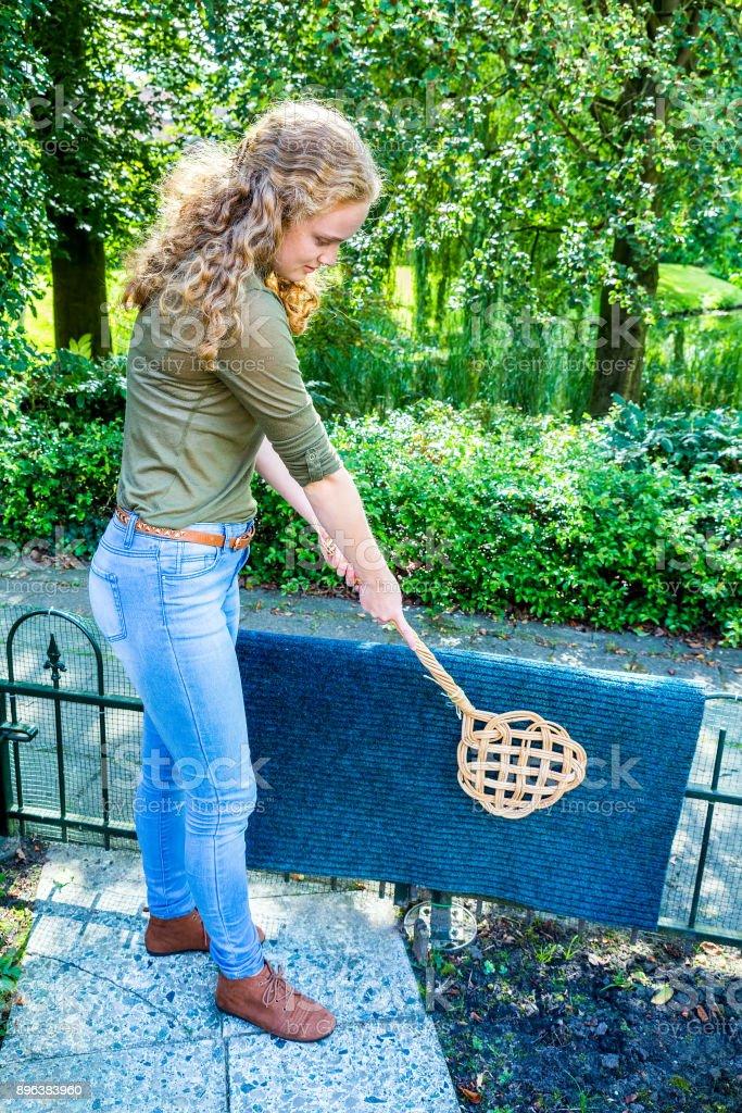 Dutch girl beating door mat with carpet beater stock photo
