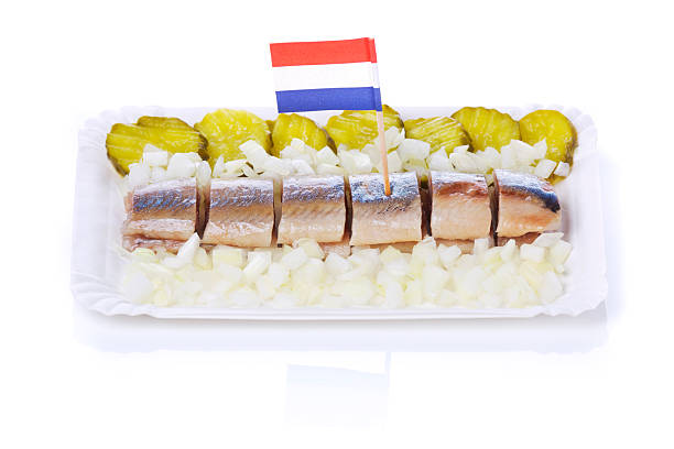 dutch herring ('haring') with onions and pickles, isolated on white - herring stock photos and pictures