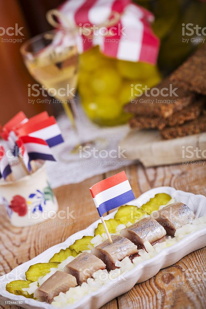 Dutch herring ('haring') with onions and pickles on rustic table royalty-free stock photo