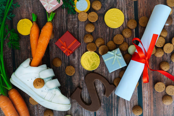 Dutch holiday Sinterklaas background with children shoe, carrots for Santa's horse, gifts, traditional sweets pepernoten and chocolate letter. Flat lay with copy space. Dutch holiday Sinterklaas background with children shoe, carrots for Santa's horse, gifts, traditional sweets pepernoten and chocolate letter. Flat lay with copy space. sinterklaas stock pictures, royalty-free photos & images