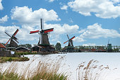 Dutch landscape with four windmills on the Zaanse Schans with the Zaan water