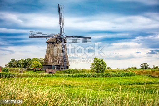 old antique windmill against a cloudy sky; South Holland