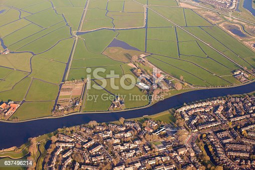 istock Dutch landscape with village, green fields and canal 637496214