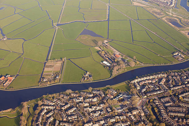 dutch landscape with village, green fields and canal - pays bas photos et images de collection
