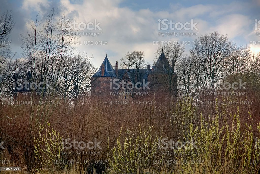 Dutch Loevestein Castle hidden behind trees and bushes stock photo
