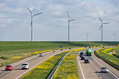 Lelystad, The Netherlands- April 5, 2019: Dutch motorway A6 near Lelystad with wind turbines and blooming rapeseed