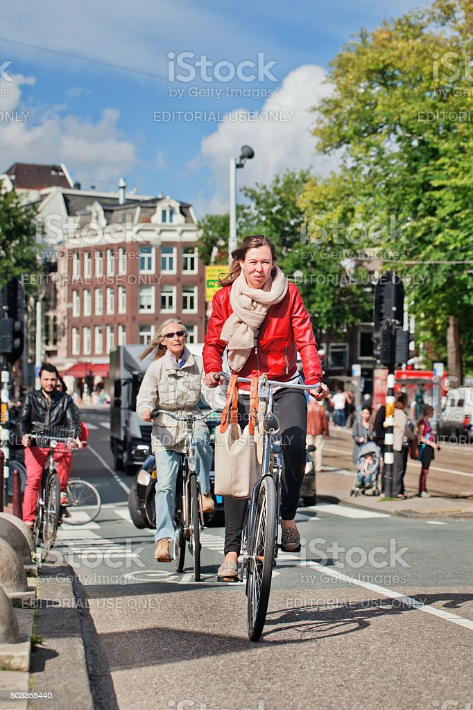 Dutch people cycling in sunny Amsterdam city center stock photo