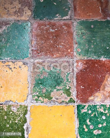 Dutch Style: Antique Floor Tiles in Oranges, Greens, Yellows. Close-up. Shot in Friesland.