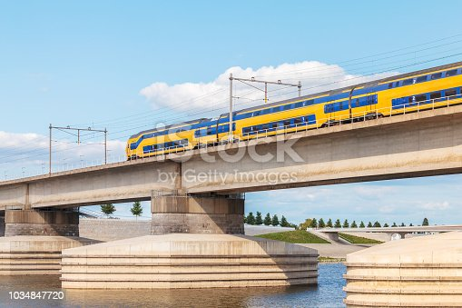 Dutch train crossing the sideskirts of the river Waal in front of the city of Nijmegen, The Netherlands