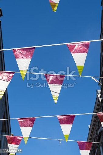 istock Dutch triangular flags on a ribbon, in red, white and yellow, of traditional festival named Carnaval, like Mardi Gras, in 's-Hertogenbosch, Oeteldonk with a blue sky 1283388737