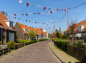Marken, Netherlands, May 6, 2016: View of the typical houses in this village which is located on a peninsula in the Markermeer and was formerly an island in the Zuiderzee.  In the background is the bell tower of the protestant church Grote Kerk.