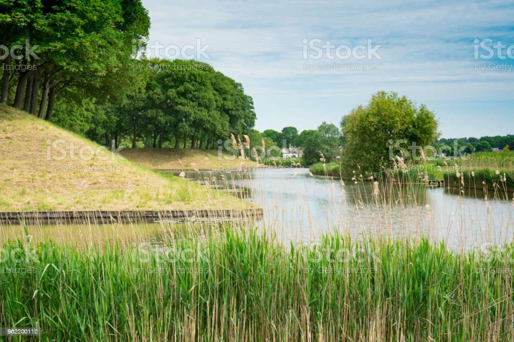 dutch water landscape with dike and trees in fortified village Klundert, The Netherlands stock photo