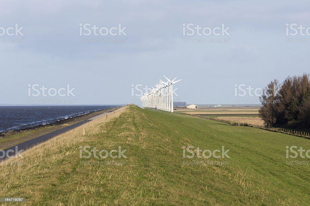 Dutch wind turbines along a straight dike royalty-free stock photo