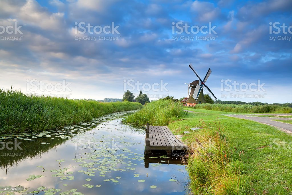 Dutch windmill by river with reflected blue sky royalty-free stock photo