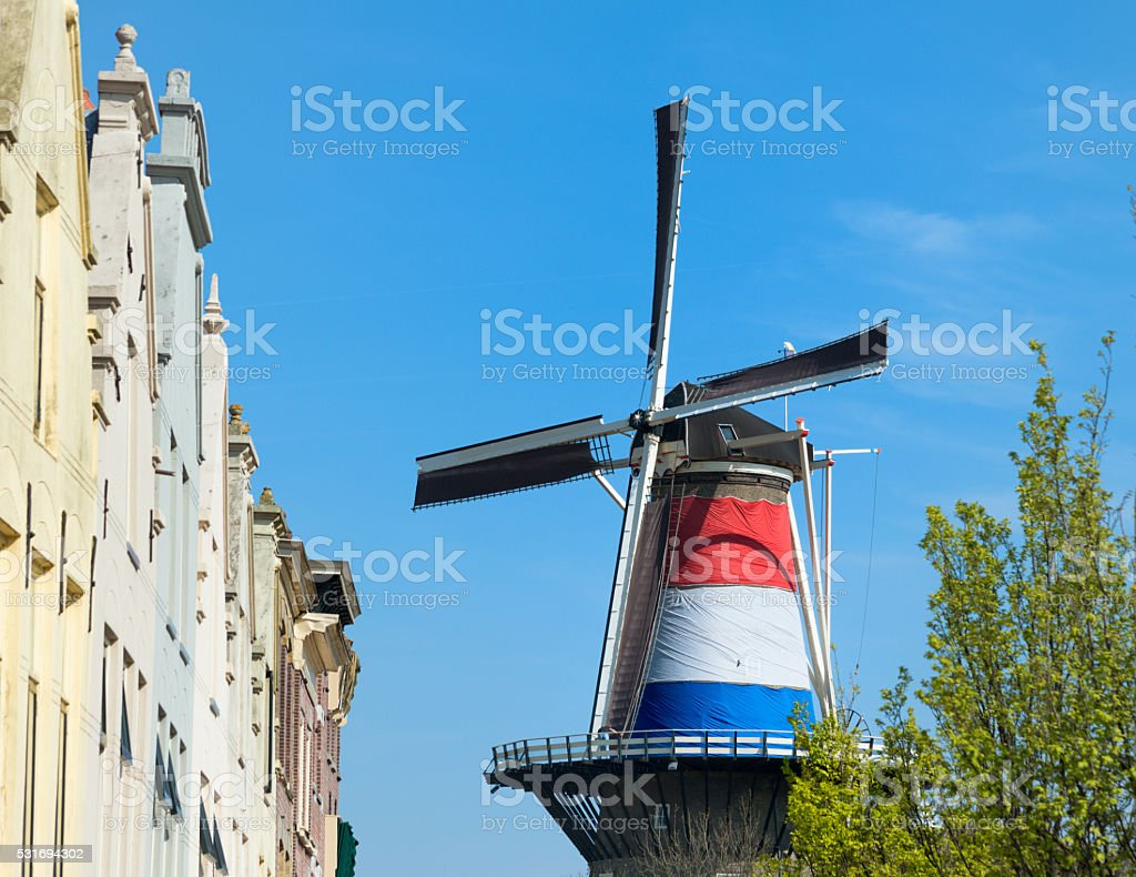 Dutch windmill in the city of Leiden. Windmill with giant dutch flag in the centre of Leiden. Architecture Stock Photo