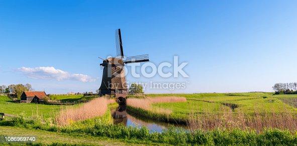 Dutch windmill along a canal under a nice blue sky. Location is Schermerhorn, Netherlands