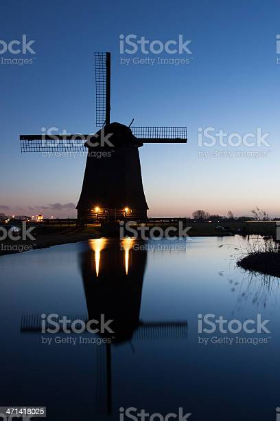 Photo of Dutch windmill with reflection at night