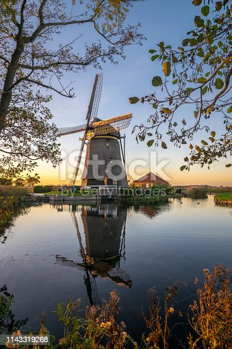 Scenic view of the dutch countryside near Leiden with a windmill near a small lake.