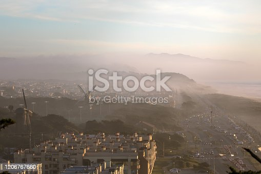 Beautiful old Dutch windmills and Ocean Beach in foggy San Francisco, California. Taken right before sunset, idyllic lighting. San Francisco Sunset District in background. Golden Gate Park, outdoors, sunny. Conservation Wind Power - Environment