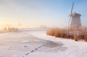 Traditional Dutch windmills on a beautiful frosty and foggy morning.