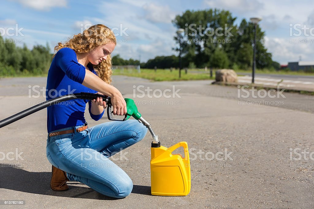 Dutch woman fueling jerrycan with petrol hose stock photo