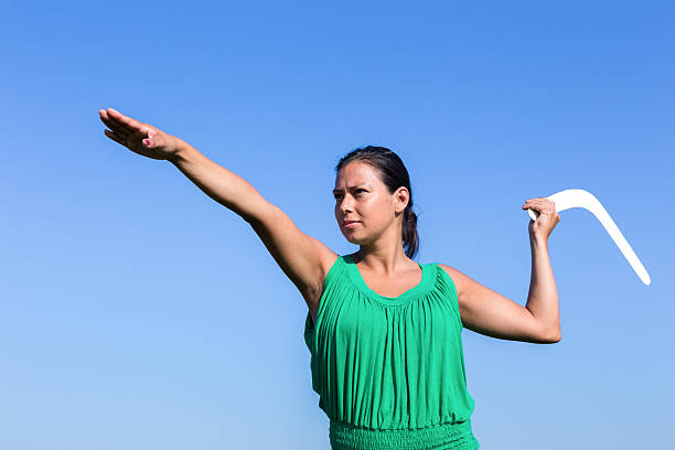 Dutch woman throwing boomerang in blue sky - Photo