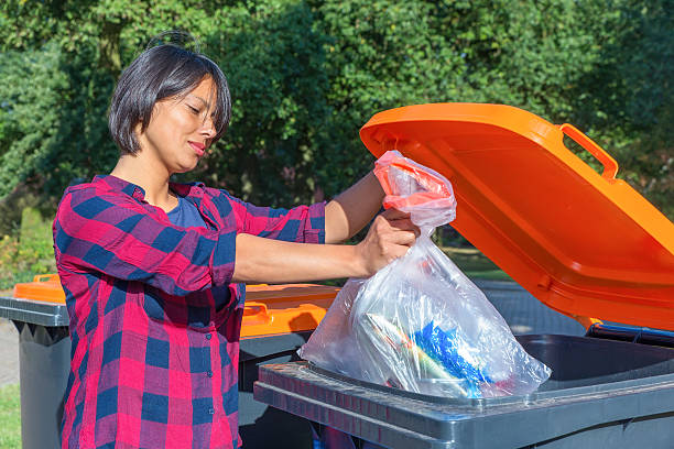 Dutch woman throwing plastic garbage in thrash bin ストックフォト