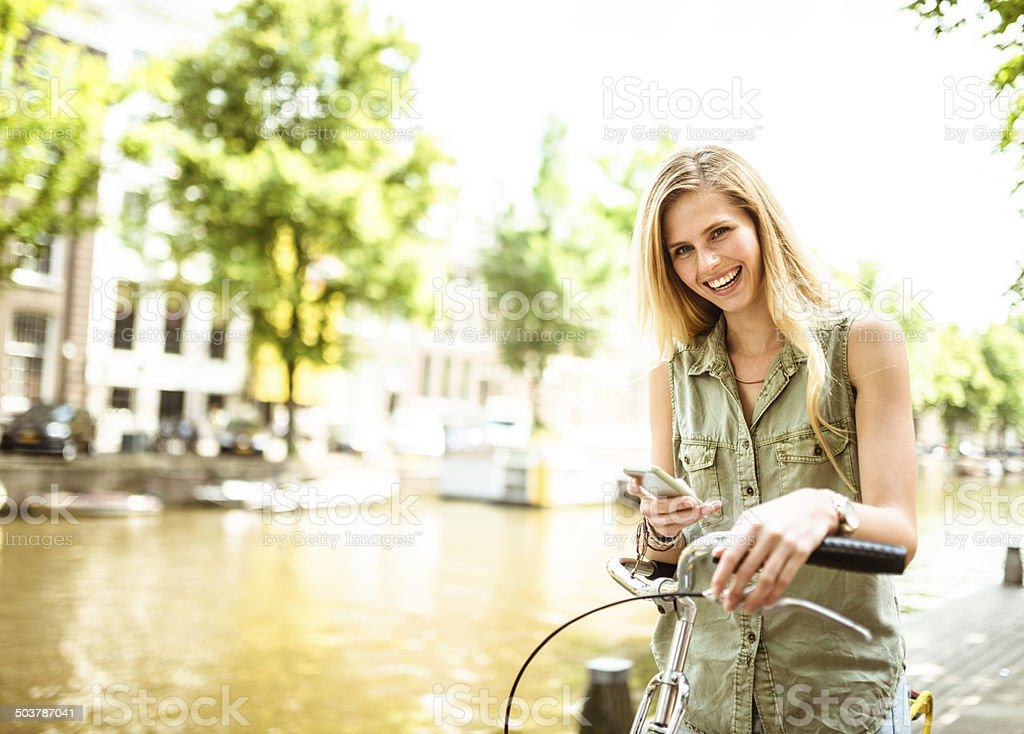 Dutch woman with bicycle in amsterdam text messaging stock photo