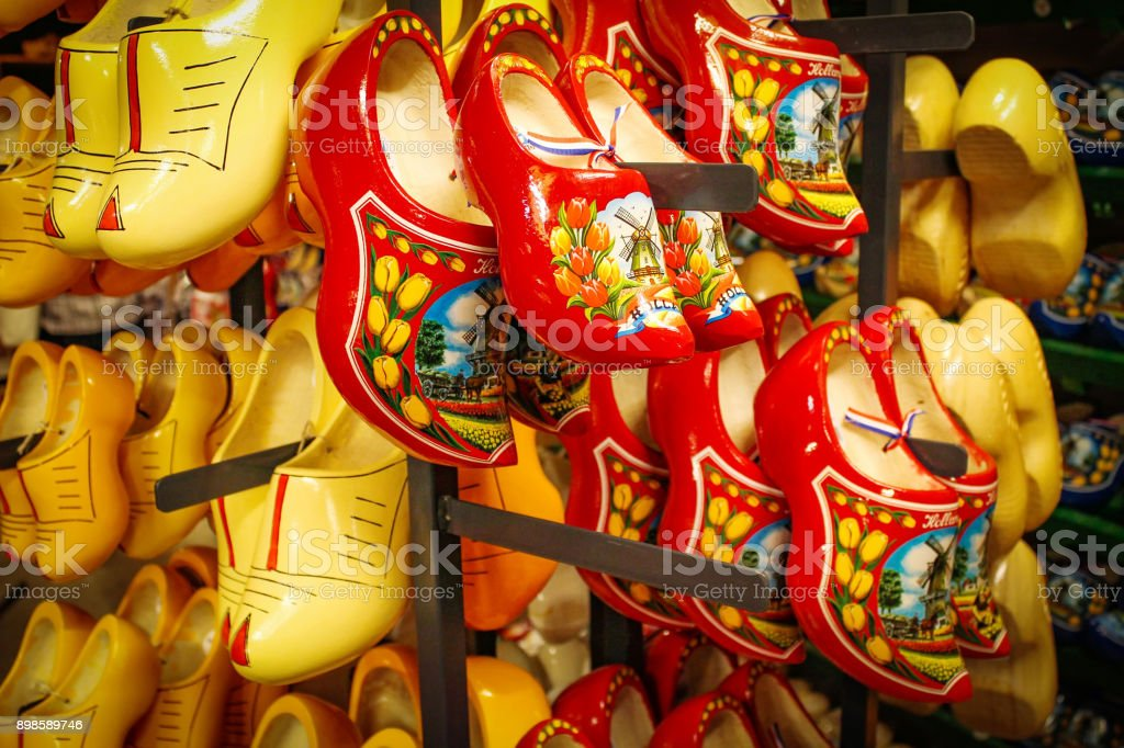 Dutch wooden shoes in the souvenir shop. Red and yellow Clog and Klomp in the storefront. Wooden klompen stock photo