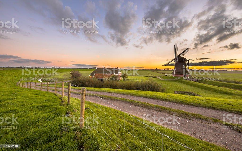 Dutch Wooden windmill in flat grassy landscape stock photo