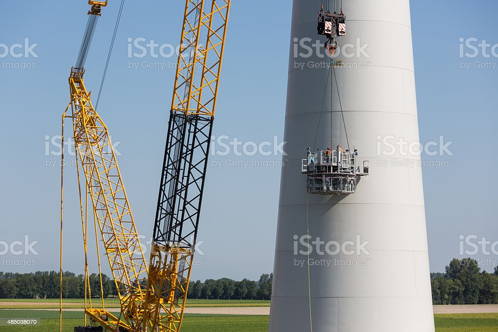 Dutch workers busy with the constuction of a new windturbine stock photo
