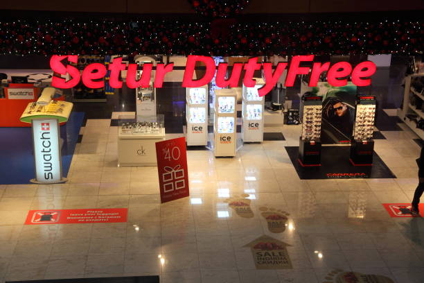 duty free at the international airport. shopping pavilion for the sale of goods to passengers. store shelves with cigarettes, alcohol, perfume and other products. reddish decorated led lights in the store. - cigarettes in duty free foto e immagini stock