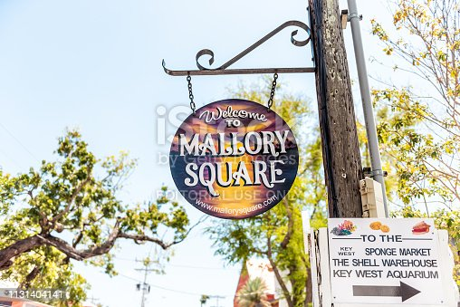 Key West, USA - May 1, 2018: Duval street closeup of Welcome to Mallory Square shopping sign architecture with nobody in Florida city travel, sunny day, sky