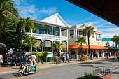Key West, Florida, USA - January 17, 2015: Pedestrians as well as two tourists riding scooters enjoy a warm January day on Duval Street in Key West, Florida